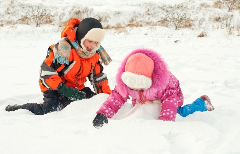 Garçon et fille jouant sur la neige photographie stock