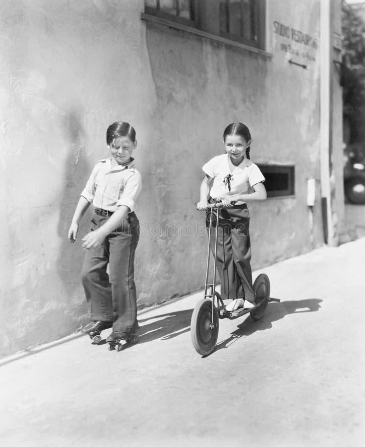 Garçon et fille jouant sur un scooter et l'autre sur des lames de rouleau (toutes les personnes représentées ne sont pas plus lon photo libre de droits