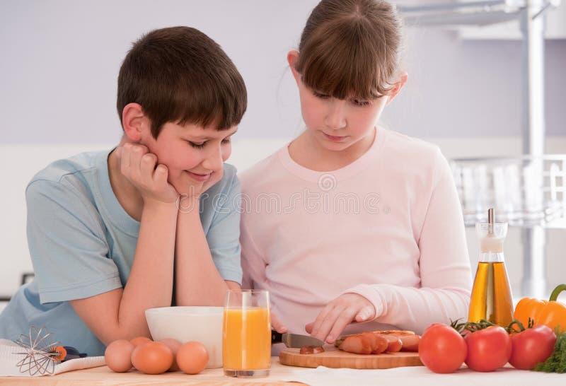 Garçon et fille mangeant de la céréale de petit déjeuner à la maison photo stock