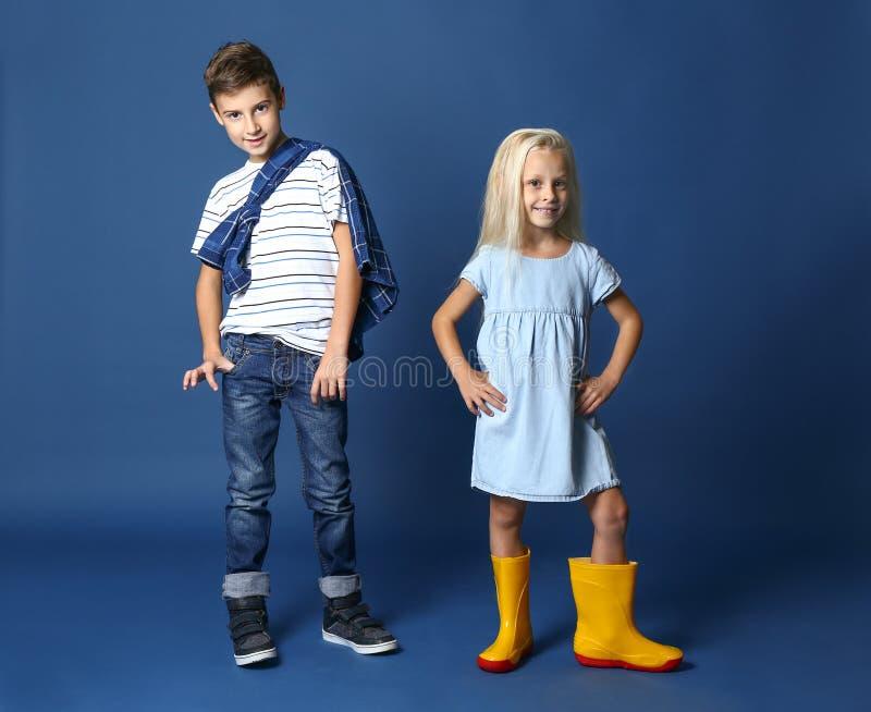 Garçon et fille mignons dans des vêtements à la mode sur le fond de couleur images stock