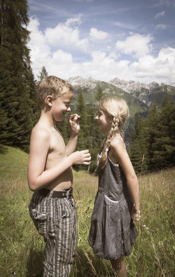 Garçon et fille mignons en montagnes dans l'amour photo libre de droits