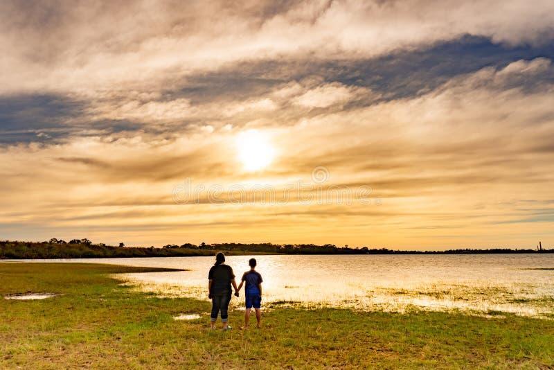 Garçon et fille regardant le coucher du soleil photographie stock