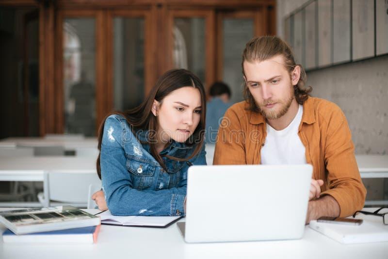 Garçon et fille regardant pensivement sur l'ordinateur portable tout en travaillant ensemble dans le bureau Jeunes étudiants s'as photographie stock libre de droits