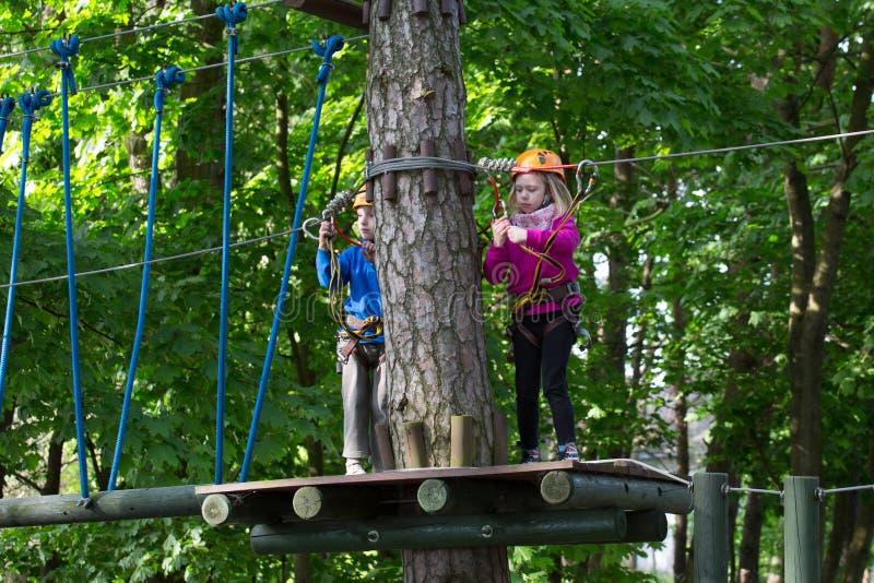 Garçon et fille s'élevant en parc d'aventure images stock