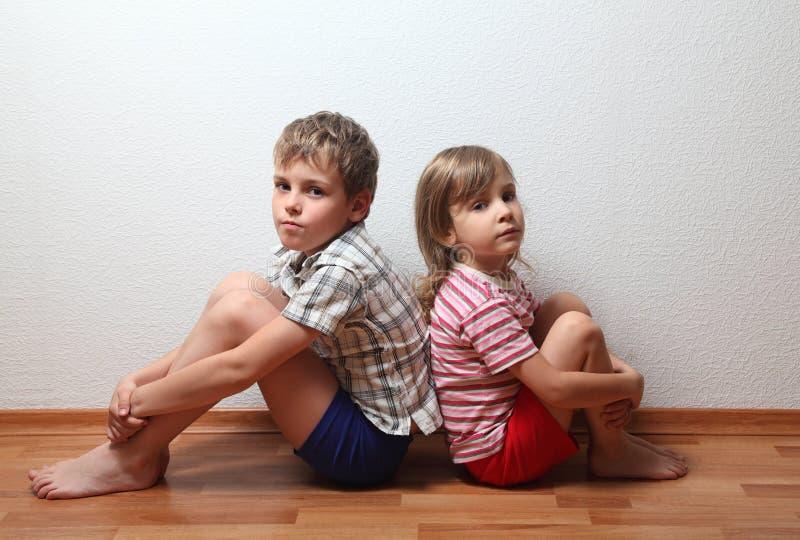 Garçon et fille s'asseyant de nouveau au dos photo libre de droits