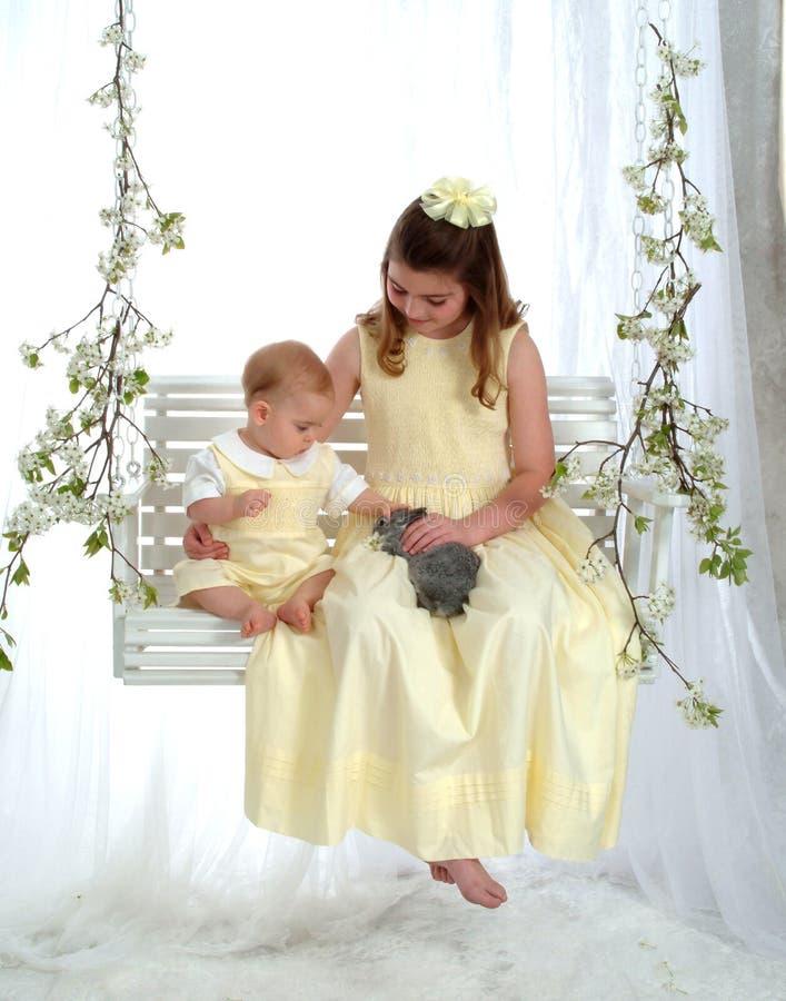 Garçon et fille sur l'oscillation avec le lapin photo stock
