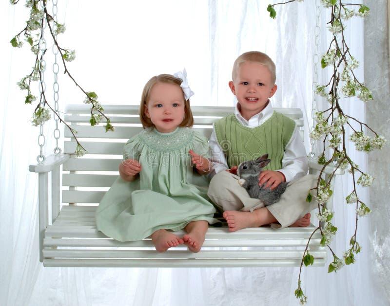 Garçon et fille sur l'oscillation avec le lapin photos stock