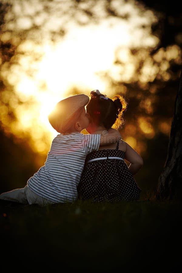 Garçon et fille sur le coucher du soleil images libres de droits