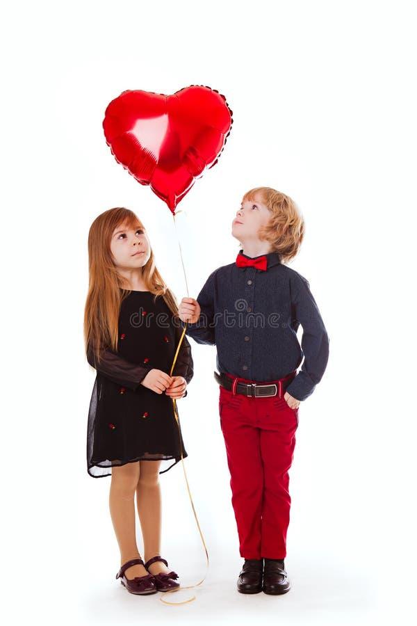 Garçon et fille sur un fond blanc tenant un coeur de rouge de ballon image libre de droits