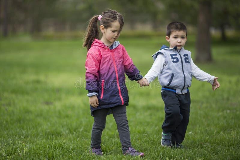 Garçon et fille tenant des mains et marchant en nature photo stock
