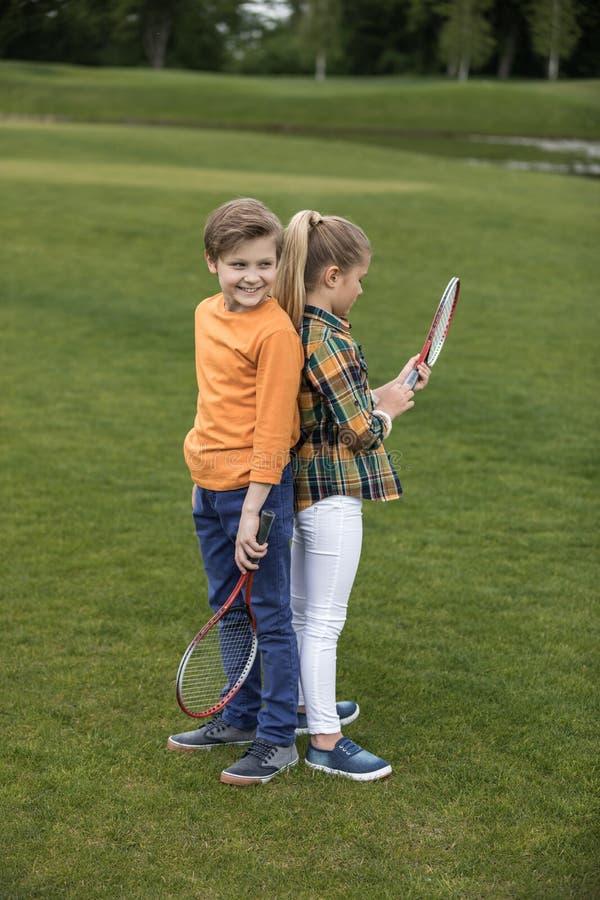 Garçon et fille tenant des raquettes de badminton tout en se tenant de nouveau au dos sur l'herbe verte photo libre de droits
