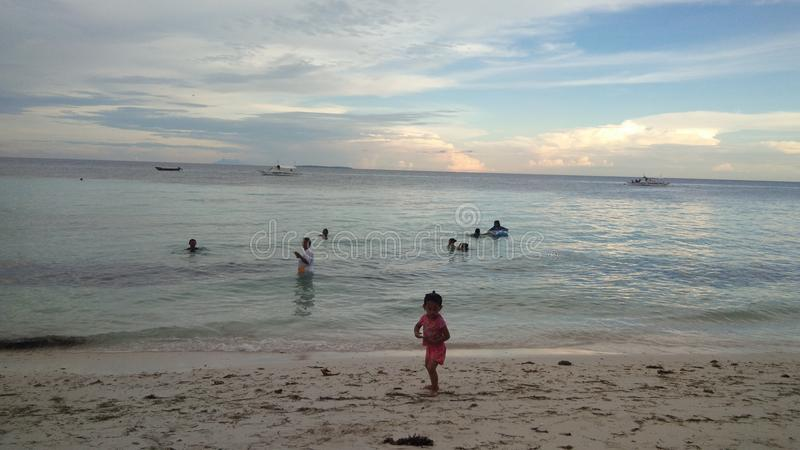 Garçon et filles s'asseyant sur le bureau surfant et le regard sur la mer bleue images stock