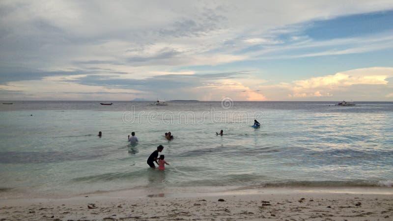 Garçon et filles s'asseyant sur le bureau surfant et le regard sur la mer bleue photographie stock libre de droits