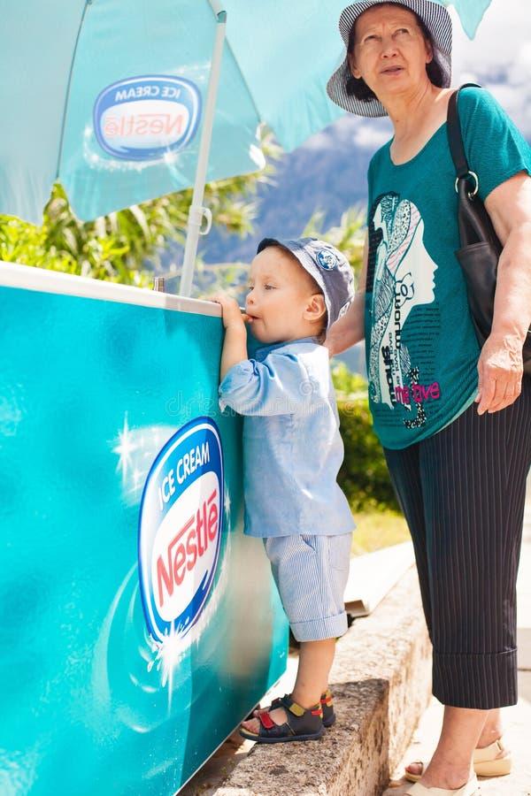 Garçon et grand-mère près du réfrigérateur avec la crème glacée  images stock