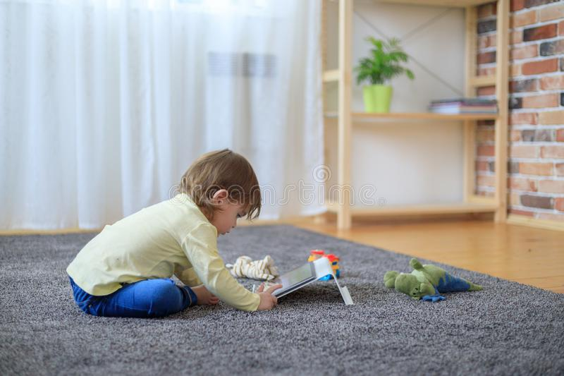 Garçon et jouets avec la tablette images stock