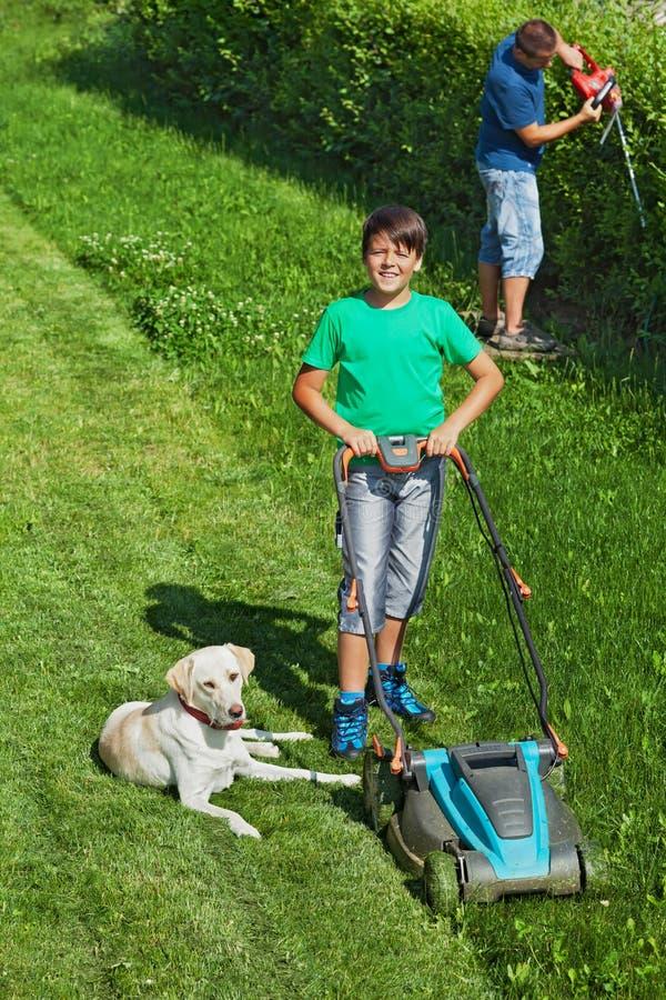 Garçon et son père fauchant la pelouse et équilibrant la haie image stock