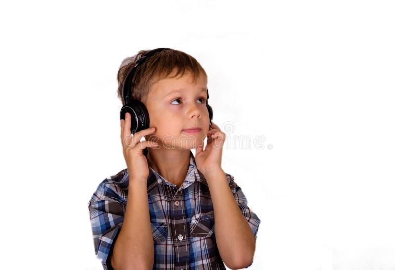 Garçon européen écoutant la musique sur des écouteurs isolat photographie stock libre de droits