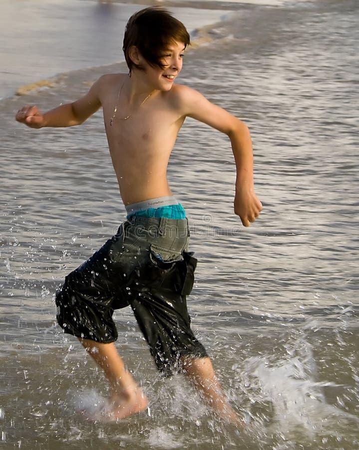 Garçon exécutant avec la marée photographie stock libre de droits