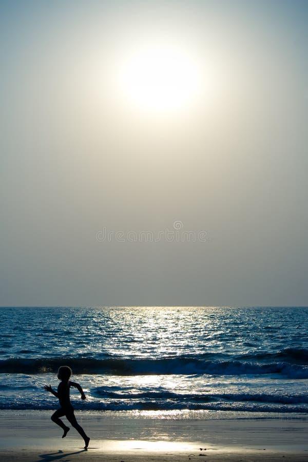 Garçon exécutant sur la plage photos libres de droits