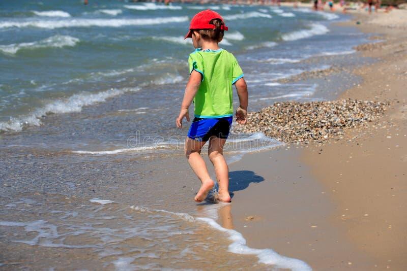 Garçon exécutant sur la plage photographie stock