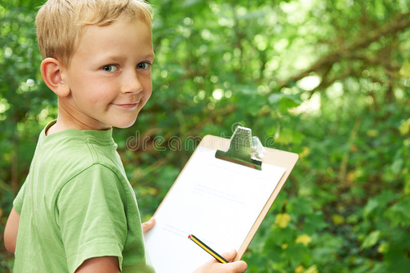 Garçon faisant des notes sur l'excursion sur le terrain de nature d'école image libre de droits