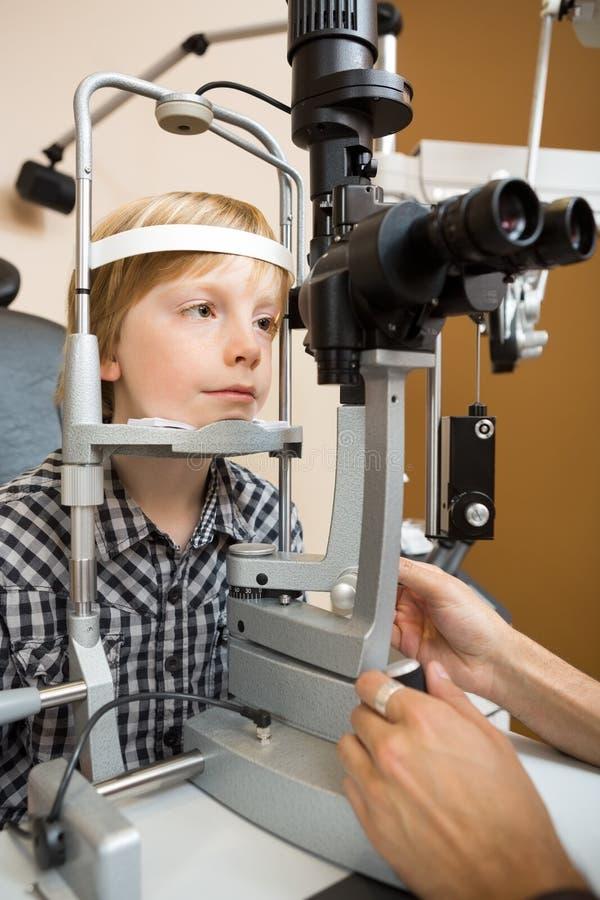 Garçon faisant examiner ses yeux avec la lampe fendue par photos libres de droits