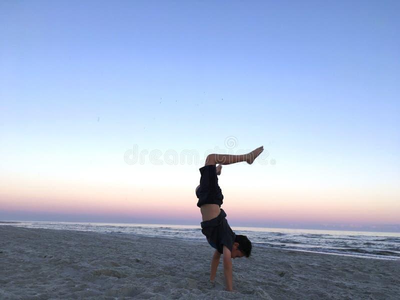 Garçon faisant l'appui renversé sur la plage photographie stock libre de droits