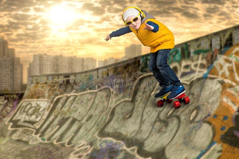 Garçon faisant les tours sur une planche à roulettes, cascades en parc de patin Le petit garçon dans le style du hip-hop images libres de droits