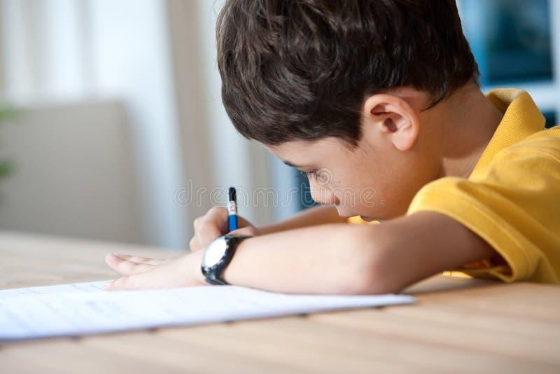 Garçon faisant son travail à la maison. images stock