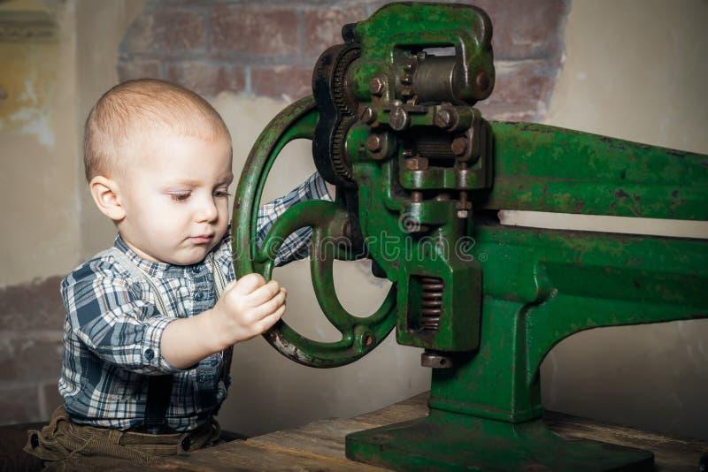 Garçon faisant tourner la roue de la machine photos libres de droits