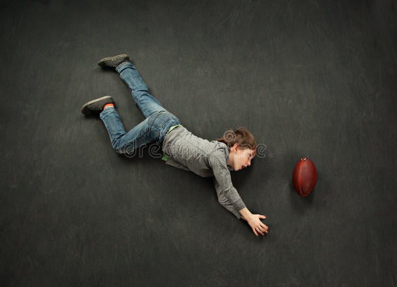 Garçon faisant un crochet de plongée pour le football photos stock