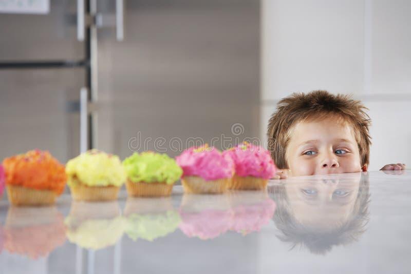 Garçon faisant une pointe au-dessus du compteur à la rangée des petits gâteaux photographie stock