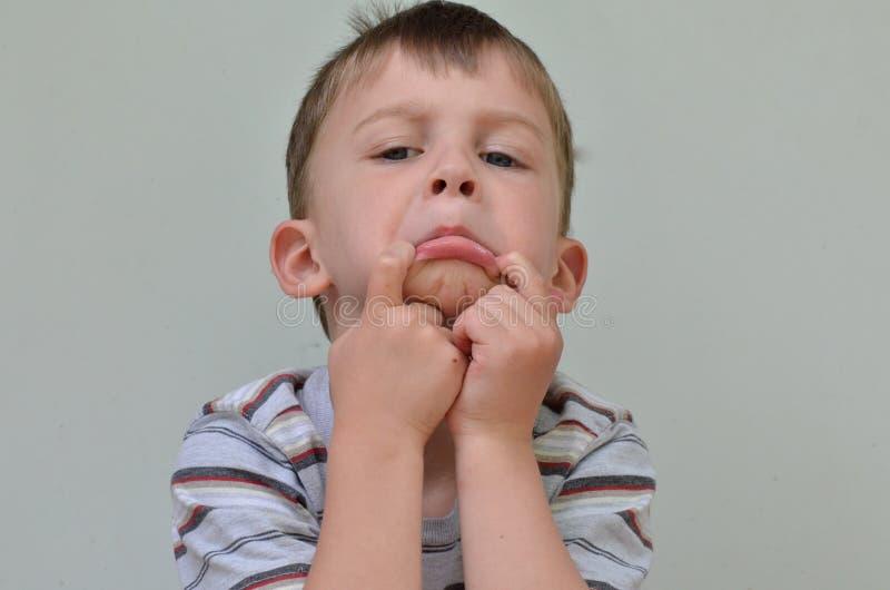 Garçon fait face triste photo stock