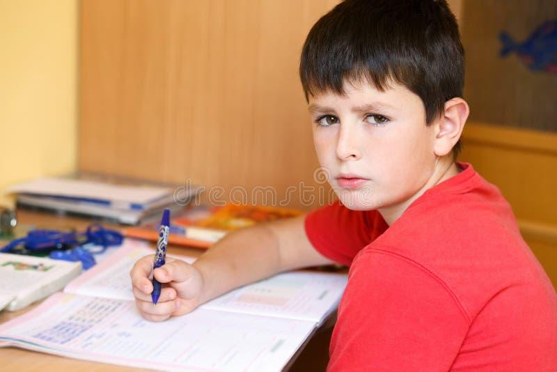 Garçon fatigué et ennuyé faisant des devoirs d'école photographie stock