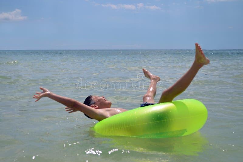 Garçon flottant en anneau vert images libres de droits