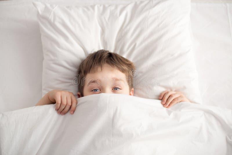Garçon gai dans le lit blanc sous la couverture blanche images libres de droits