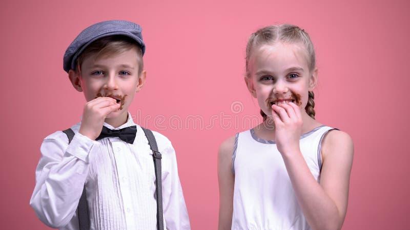 Garçon gai et fille souriant et mangeant des bonbons au chocolat, célébrant des vacances photos libres de droits