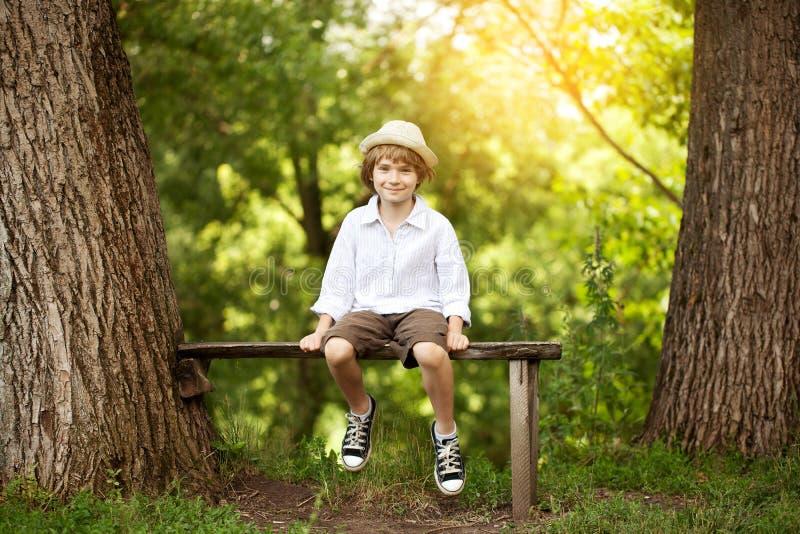 Garçon gai s'asseyant sur un banc photo libre de droits