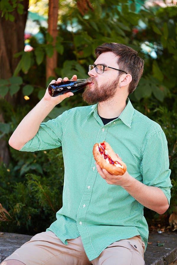 Garçon gracieux avec des glasess goûtant la nourriture délicieuse en parc Fond de nature photos libres de droits