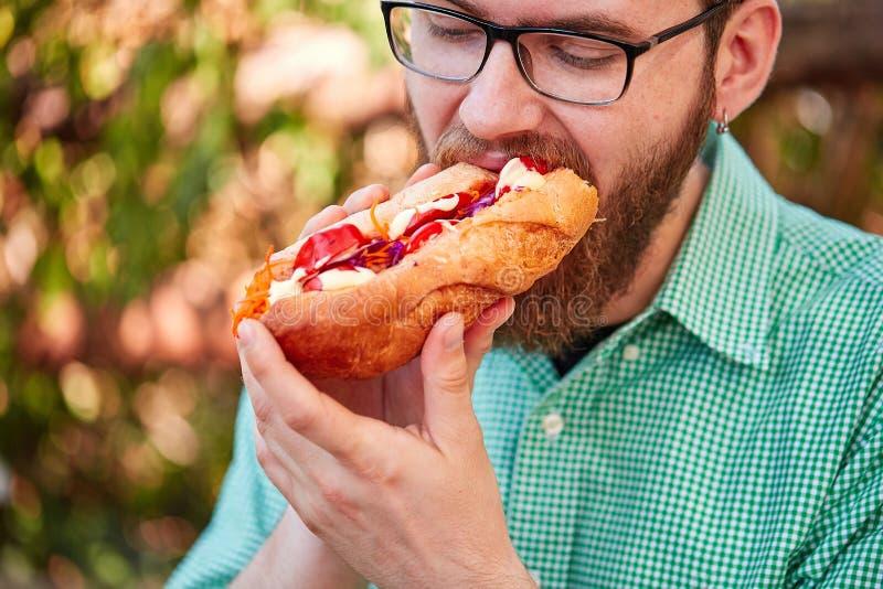 Garçon gracieux avec des glasess goûtant la nourriture délicieuse en parc Fond de nature images libres de droits