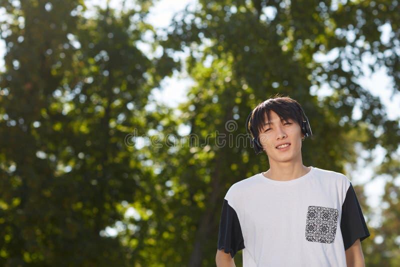 Garçon gracieux avec un écouteur noir sur un fond vert des arbres photo stock