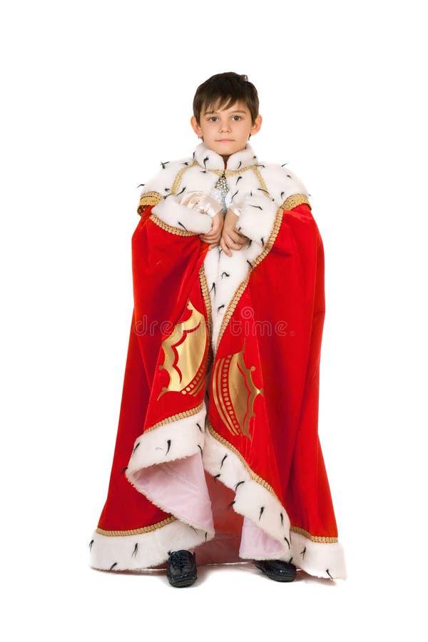 Garçon habillé dans une robe longue de roi. D'isolement photographie stock