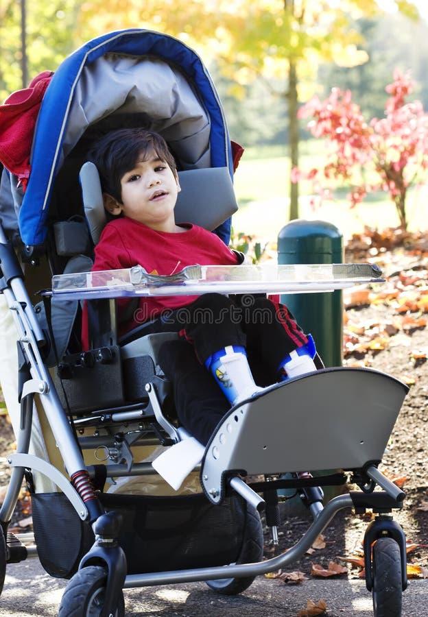 Garçon handicapé dans le fauteuil roulant médical au stationnement photos stock