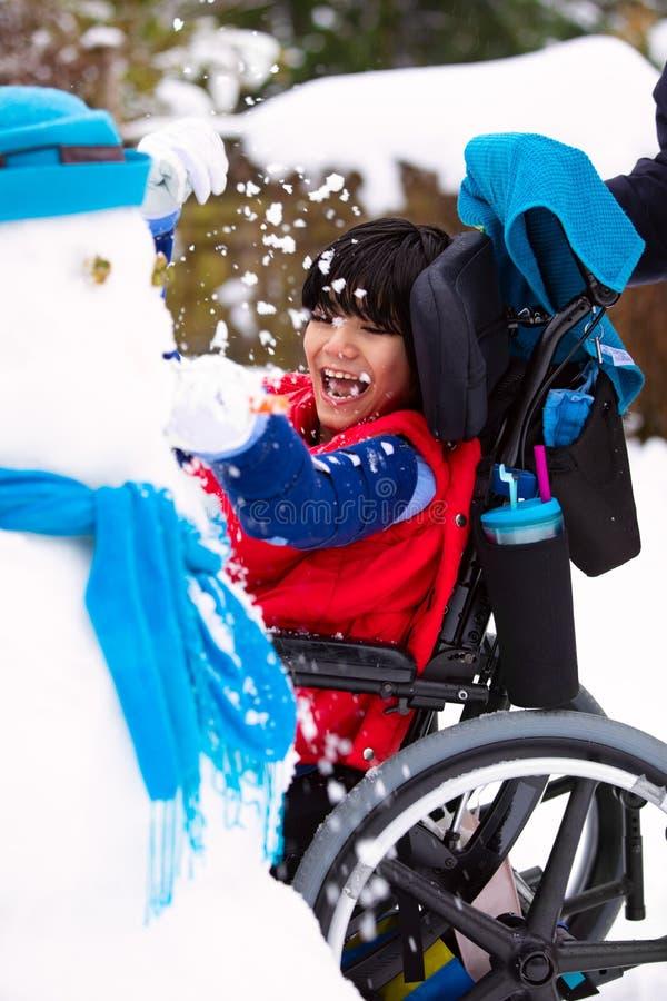 Garçon handicapé de sourire heureux dans le bâtiment de fauteuil roulant un bonhomme de neige photos libres de droits