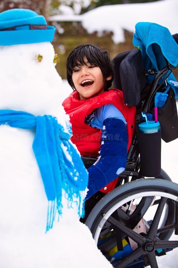 Garçon handicapé de sourire heureux dans le bâtiment de fauteuil roulant un bonhomme de neige photographie stock libre de droits