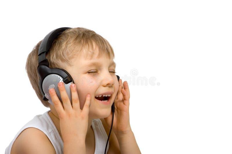 Garçon heureux écoutant avec l'écouteur photos libres de droits