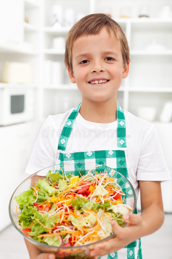 Garçon heureux avec de la salade fraîche - nutrition saine image libre de droits