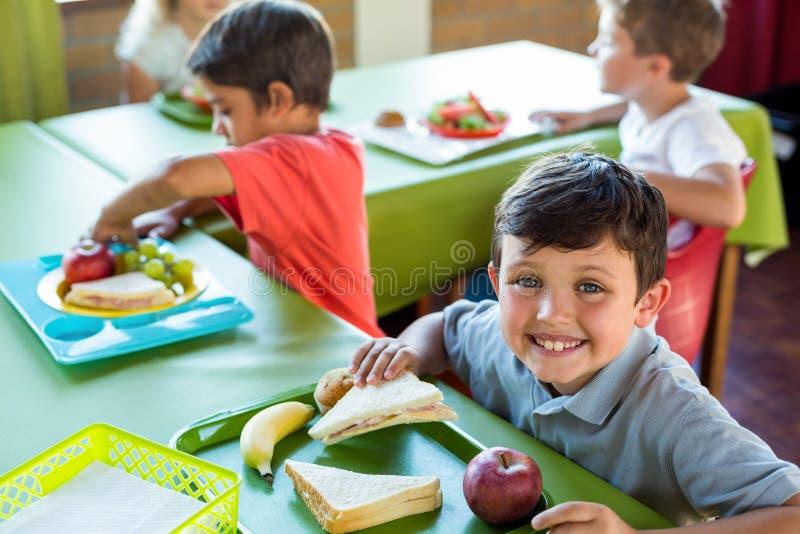 Garçon heureux avec des camarades de classe ayant le repas images libres de droits