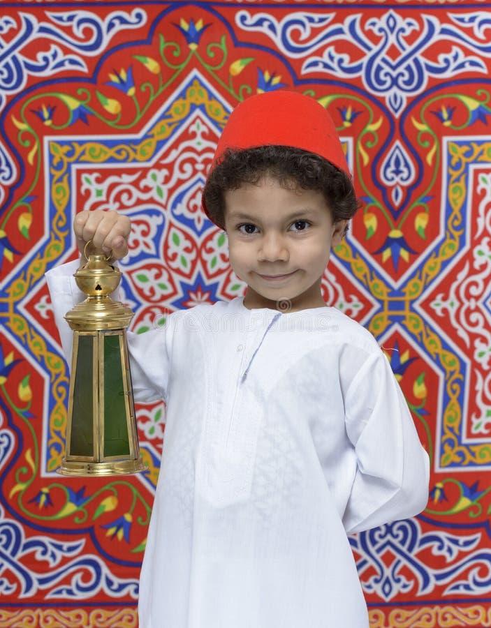 Garçon heureux avec Fez et lanterne célébrant Ramadan photographie stock libre de droits