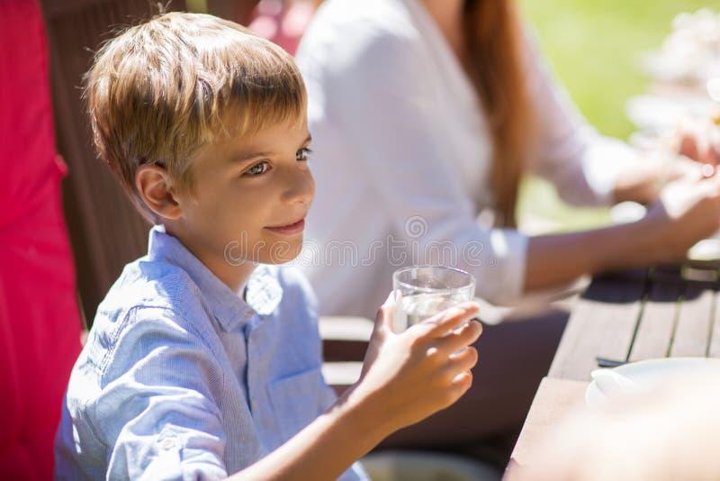 Garçon heureux avec le verre de l'eau au dîner de fête image stock